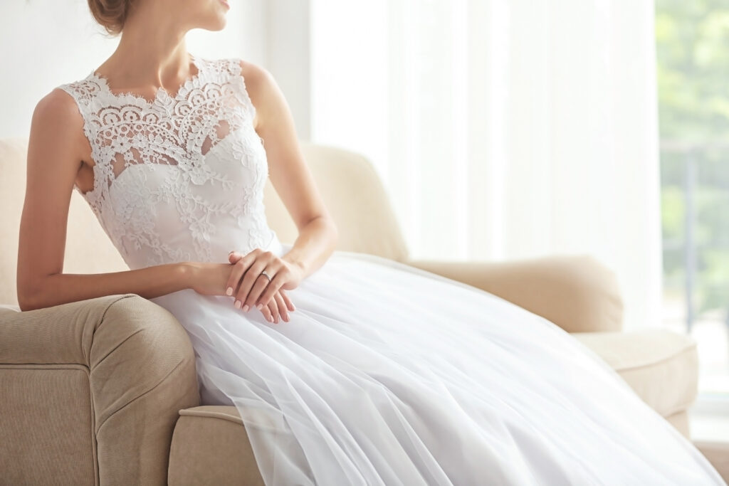 Bride in beautiful wedding gown sitting on sofa