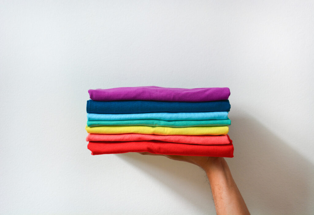 close up stack of folded multicolored t-shirt in hand